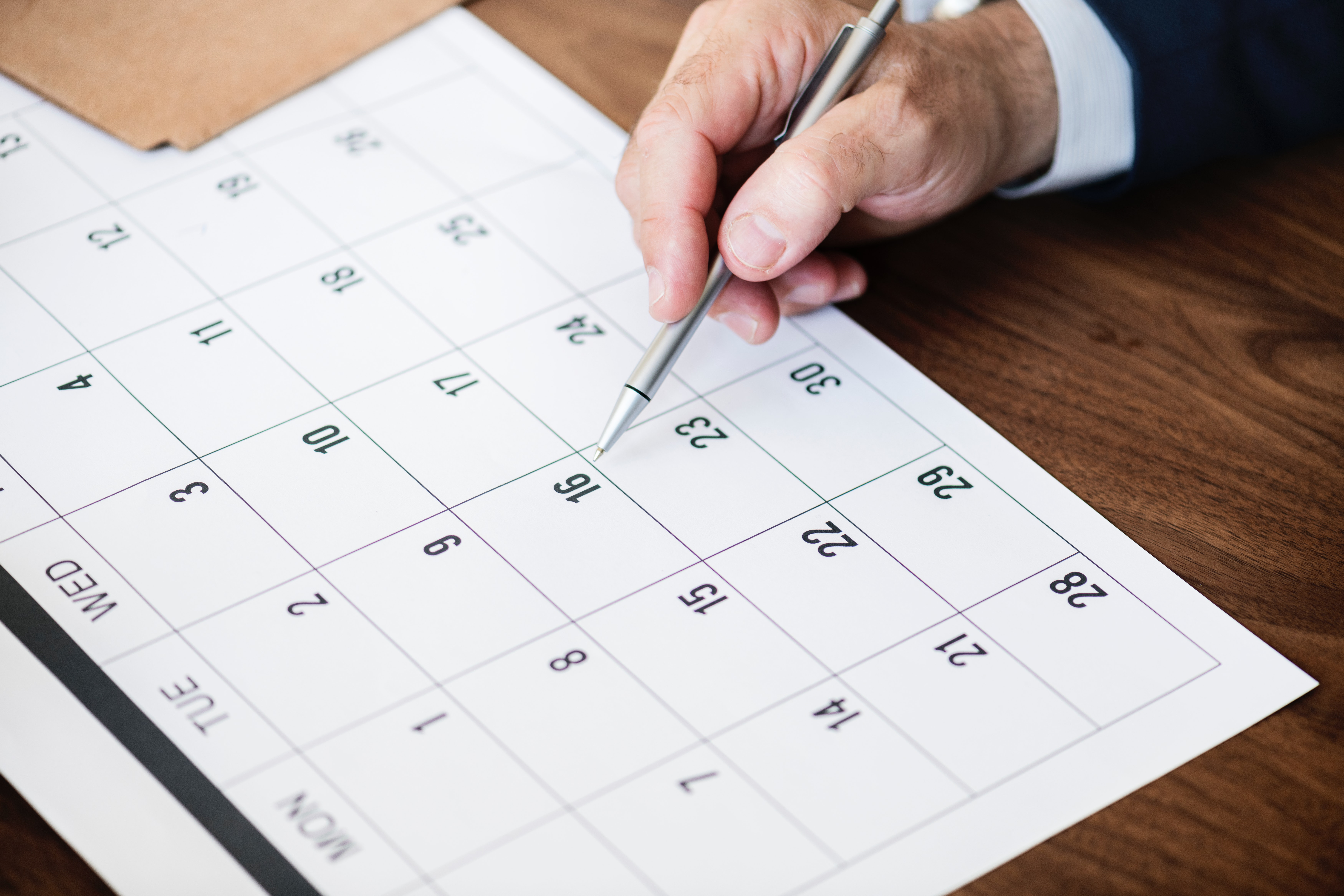 Person Pointing at Calendar with Pen