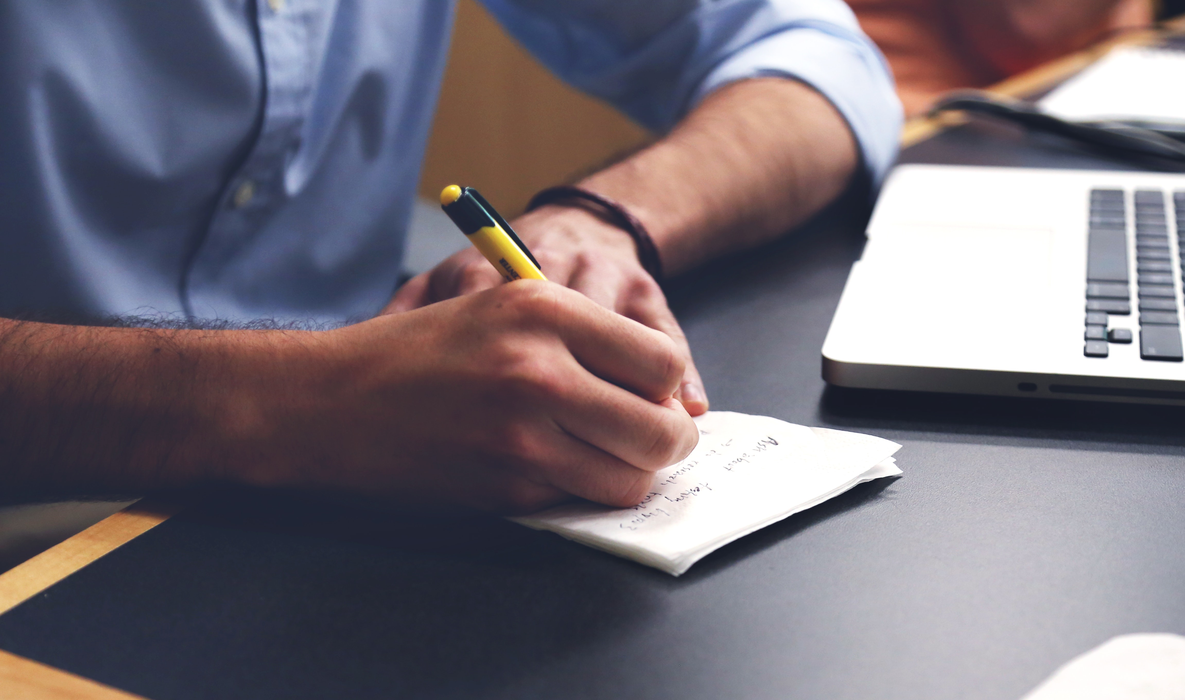 Hand Writing Notes at a Desk